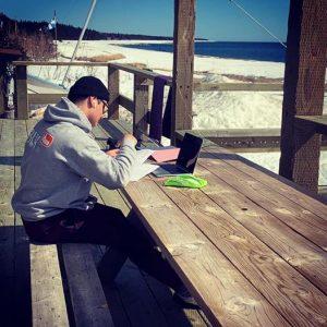 étudiant assis à l'extérieur avec son ordinateur, face à la mer