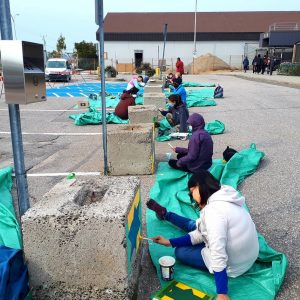 Étudiants en train de peindre sur des blocs de béton